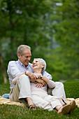Adult, Adults, Affection, Amusement, Bond, Bonding, Bonds, Caucasian, Caucasians, Color, Colour, Contemporary, couple, couples, Daytime, embrace, embracing, exterior, female, Fondness, Full body, Full length, Full-body, Full-length, Fun, Grass, grin, grin
