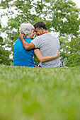 Adult, Adults, Affection, back view, Bond, Bonding, Bonds, Caucasian, Caucasians, Color, Colour, complicity, Contemporary, couple, couples, Daytime, embrace, embracing, exterior, female, Fondness, Grass, Gray-haired, Grey hair, Grey haired, Grey hairs, Gr