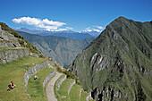 Visitors sitting on terraces at Machu Picchu, Peru
