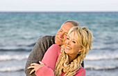 Adult, Adults, Affection, beach, beaches, Bond, Bonding, Bonds, Caucasian, Caucasians, Closed eyes, Color, Colour, Contemporary, couple, couples, Daytime, embrace, embracing, exterior, Eyes shut, female, Fondness, grin, grinning, happiness, happy, hug, hu