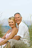 Adult, Adults, Affection, beach, beaches, Bond, Bonding, Bonds, Caucasian, Caucasians, Color, Colour, Contemporary, couple, couples, Daytime, embrace, embracing, exterior, Facing camera, female, Fondness, Grass, Grasses, grin, grinning, happiness, happy,