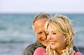 Adult, Adults, Affection, beach, beaches, Bond, Bonding, Bonds, Caucasian, Caucasians, Close up, Close-up, Closeup, Color, Colour, Contemporary, couple, couples, Daytime, embrace, embracing, exterior, face, faces, female, Fondness, grin, grinning, happine