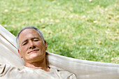 Adult, Adults, Calm, Calmness, Caucasian, Caucasians, Chill out, Chilling out, Closed eyes, Color, Colour, Contemporary, Daytime, exterior, Eyes shut, Garden, Gardens, Gray-haired, Grey hair, Grey haired, Grey hairs, Grey-haired, Hammock, Hammocks, Head &