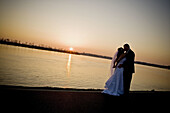 Wedding couple kissing, wide angle, Silhouette, downtown river front