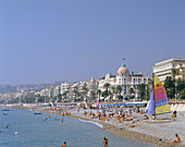 Beach scene with Hotel Negresco, Nice, Cote d'Azur, France
