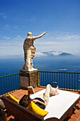 Young woman lying reading at a terrace with sea view, Capri, Italy, Europe