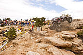 View towards a racing car which is driving over a rock at the Rock Crawling Race, Rock Crawling, Moab, Utah, USA