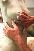 Hands of an artist shaping a clay sculpture of a female body  Richard Smith, Aptos, California, USA