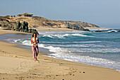 Blick auf eine Frau die am Strand entlang läuft und ihr 5 Monate altes Baby trägt, Nine Palms, Baja California Süd, Mexiko