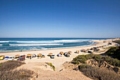 View from above towards a surfbeach with people camping, Nine Palms, Baja California Sur, Mexico