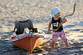 A 14 month old girl with a stick in her hand next to a sea kayak on the beach, Punta Conejo, Baja California Sur, Mexico
