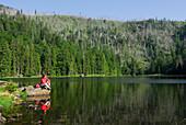 Woman sitting on lake Rachelsee, Bavarian Forest National Park, Lower Bavaria, Bavaria, Germany