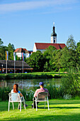 Couple sitting near pond in spa gardens, Bad Koetzting, Bavarian Forest, Upper Palatinate, Bavaria, Germany