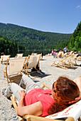 Woman sunbathing in beach chair, lake Grosser Arbersee, Bavarian Forest National Park, Lower Bavaria, Bavaria, Germany