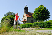 Female cyclist near chapel, Bad Koetzting, Bavarian Forest, Lower Bavaria, Bavaria, Germany