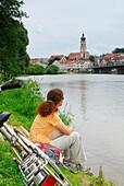 Woman sitting on Regen riverbank, Roding, Upper Palatinate, Bavaria, Germany
