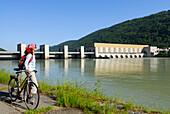Female cyclist near river Danube, Run-of-the-river hydroelectricity Jochenstein, Danube Cycle Route Passau to Vienna, Upper Austria, Austria