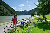 Woman near bicycle stand, Schloegener Schlinge, Danube cycle route Passau to Vienna, Schloegen, Upper Austria, Austria