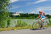 Female cyclist riding along Danube river, Persenbeug castle in background, Danube Cycle Route Passau to Vienna, Persenbeug, Lower Austria, Austria