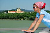 Female cyclist riding along Danube river, Melk abbey in background, Danube Cycle Route Passau to Vienna, Wachau, Lower Austria, Austria
