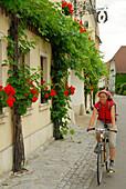 Female cyclist passing house, Danube Cycle Route Passau to Vienna, Wachau, Lower Austria, Austria