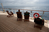 Passengers sitting in deck chairs on the promenade deck, life buoy, cruise liner, Queen Mary 2, Atlantic ocean