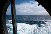 View of the Atlantic ocean and waves through a porthole, Cruise liner Queen Mary 2