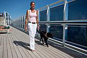 Cruise liner, Queen Mary 2, passenger taking her dog for a walk on the sun deck, Transatlantic