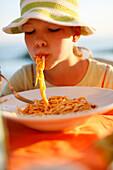 Mädchen isst Spaghetti, Formentera, Balearen, Spanien