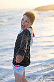 Girl on the beach in the evening light, laughing, Es Arenals, Formentera, Balearic Islands, Spain