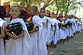 Young Buddhist monks in white robes holding bowls in queue for lunch at 10am, General, people, Burma