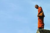 Monk at Angkor Wat in orange robe against blue sky, Siem Reap, near, Cambodia