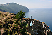 View at Cape Choboi on Olchon Island with man crossing rock window, Lake Baikal, Russian Federation
