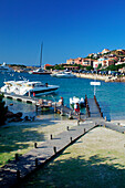Marina and jetties with hillside town in background, Porto Cervo, Sardinia, Italy
