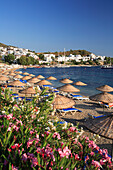 View over beach with sunshades to town and Outer Harbour, Bodrum, Aegean, Turkey