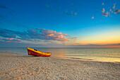 Beach scene with boat at sunset, Gdansk, near, Poland
