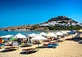 Beach scene with view of Lindos town and hilltop acropolis, Lindos, Rhodes Island, Greek Islands