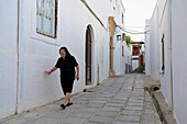 Street scene in the Old Town with old lady in black, Lindos, Rhodes Island, Greek Islands