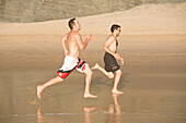 Zwei Maenner laufen, sprinten, Strand Praia do Castelejo, Vila do Bispo, Algarve, Portugal