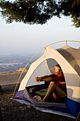 Young women waking up and stretching in her tent, Mount Foia, 902 meters above sea level, Serra de Monchique, MR, Monchique, Algarve, Portugal