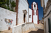 Misericordia church in Silves, Women hanging up washing on the washibng line, Silves, Algarve, Portugal