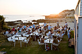Tourists dining in a fish Restaurant on the beach at sunset, Praia do Evaristo, Albufeira, Algarve, Portugal