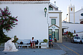 Yong women using her laptop, notebook, using free internet access, W-LAN, white church and village square, Alcoutim, Algarve, Portugal