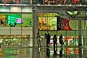 Downtown Bangkok, Siam Center, Menschen auf der Plattform vor abendlich beleuchtetem Shopping Center, Thailand, Asien