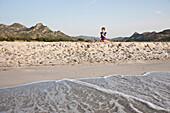 Middle-aged woman having breakfast on the beach, Berchidda, Siniscola, Sardinia, Italy, Europe