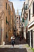 Father with child on his arm at an alley of the Old Town, Alghero, Sardinia, Italy, Europe