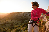 Middle-aged woman climbing and looking at the setting sun, Sassari province, Sardinia, Italy, Europe