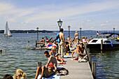 People sunbathing on jetty at lake Starnberg, Seeshaupt, Bavaria, Germany