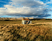 Pasture with little hut under clouded sky, Central Otago, South Island, New Zealand