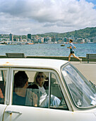 A couple in a car and a jogger on the promenade, Oriental Parade, Wellington, North Island, New Zealand